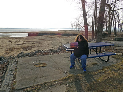 Ann sitting on the shore of Lake Champlain