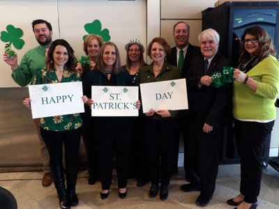 Champlain National Bank employees holding a Happy St. Patrick's Day Sign